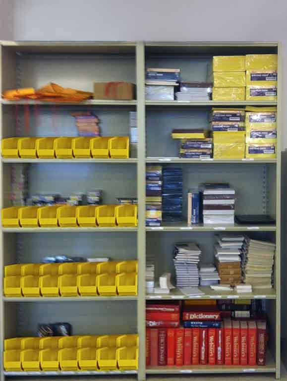 Office supplies, notepads, and dictionaries at adult literacy center on closed Aurora Storage Shelving.